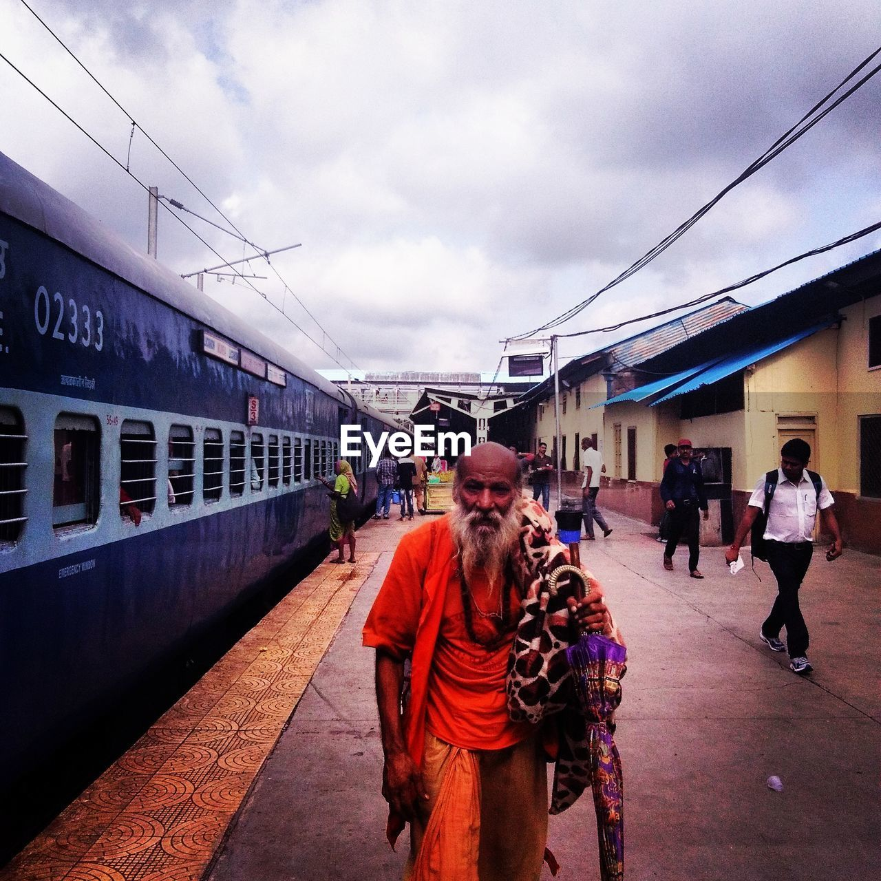real people, transportation, mode of transport, sky, men, architecture, walking, built structure, cloud - sky, train - vehicle, outdoors, lifestyles, rail transportation, public transportation, day, building exterior, women, large group of people, railroad station platform, full length, adult, people