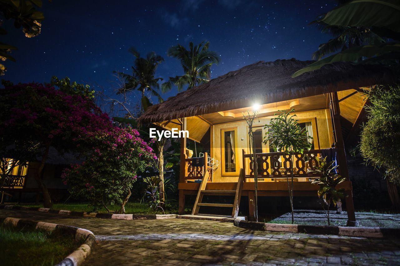 ILLUMINATED HOUSE BY TREES AT NIGHT