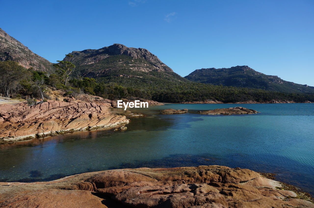 water, scenics - nature, mountain, sky, beauty in nature, tranquility, rock, tranquil scene, solid, blue, rock - object, nature, clear sky, land, no people, day, non-urban scene, sea, idyllic, outdoors, rocky coastline