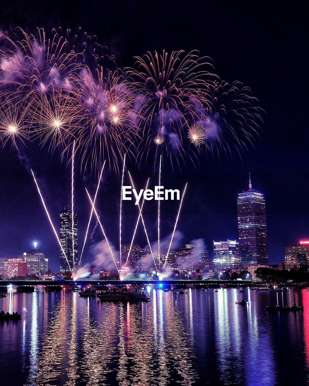 FIREWORK DISPLAY OVER RIVER IN CITY