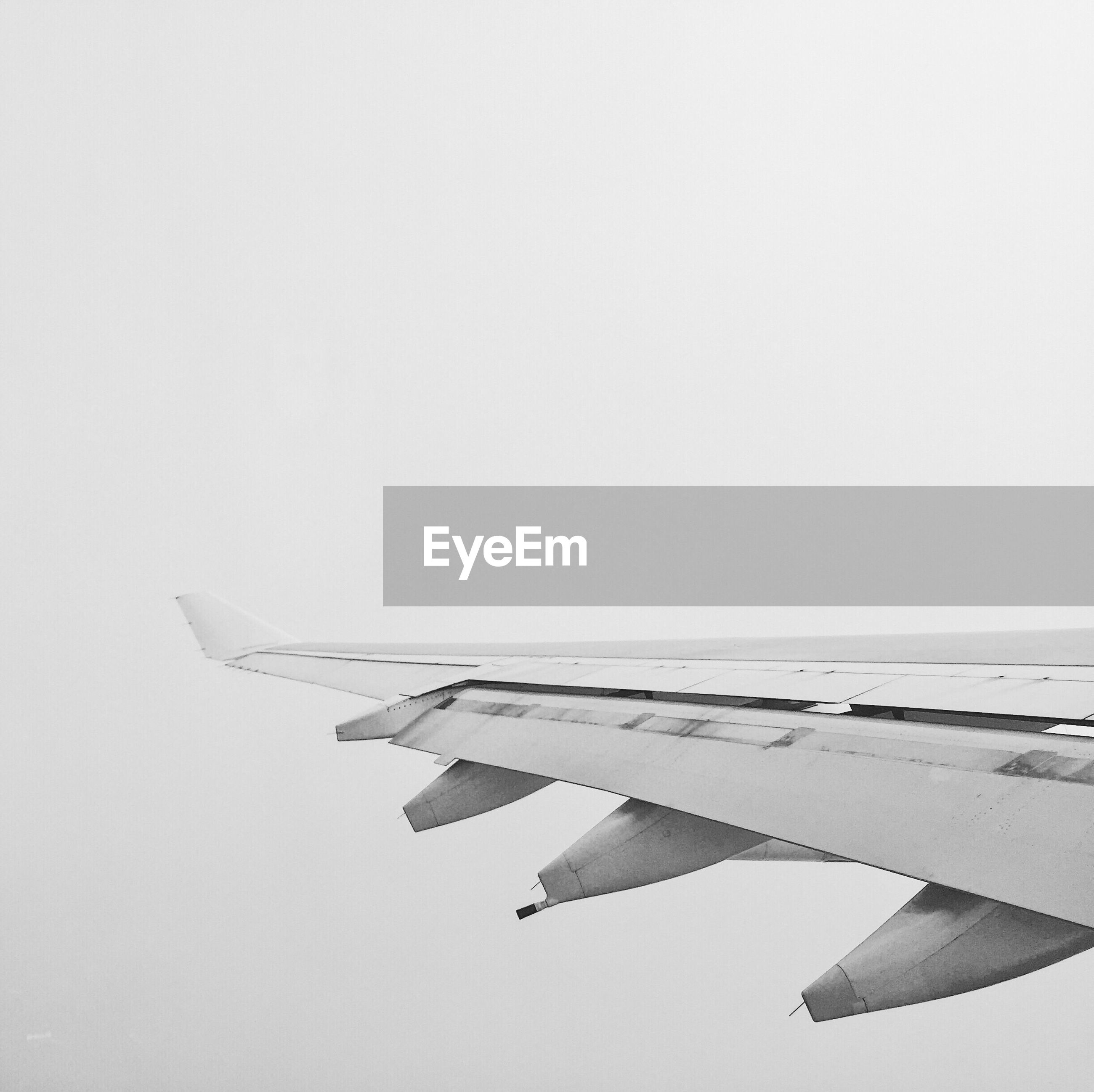 CLOSE-UP OF AIRPLANE WING AGAINST SKY