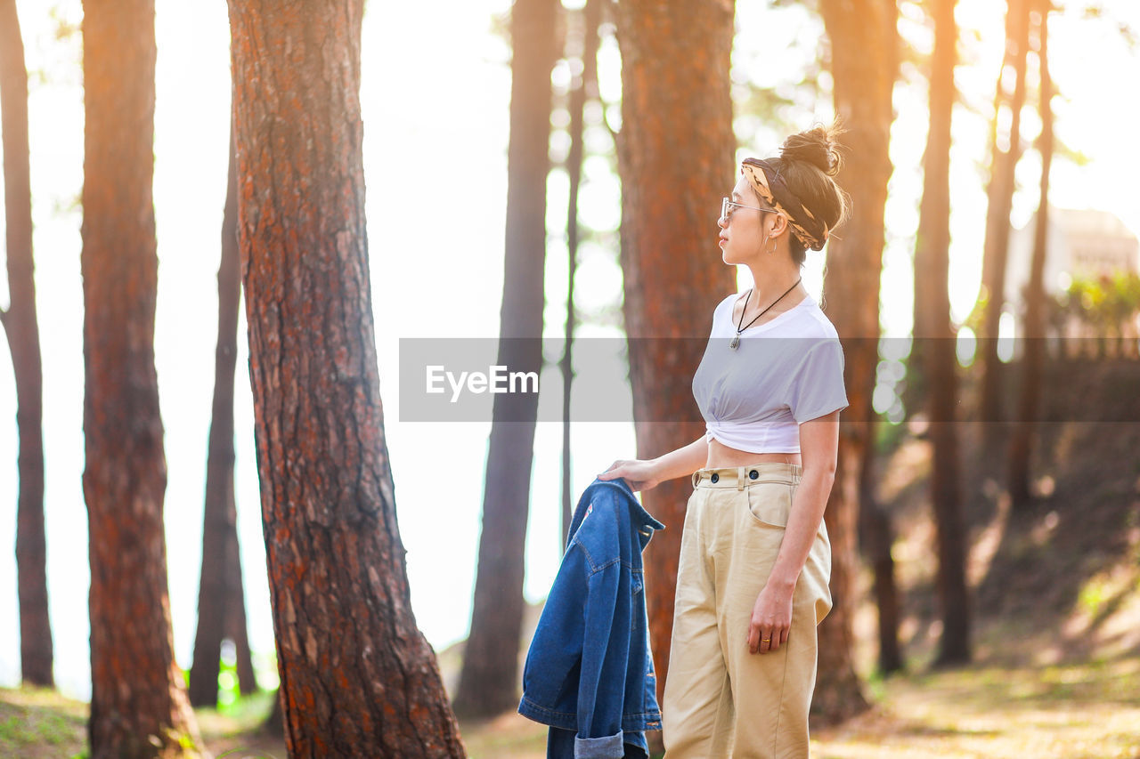 tree, trunk, tree trunk, plant, casual clothing, women, nature, adult, standing, leisure activity, three quarter length, land, forest, one person, lifestyles, day, front view, focus on foreground, young adult, outdoors, hairstyle, woodland, beautiful woman