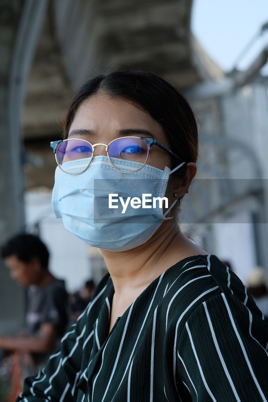 Portrait of woman wearing eyeglasses and flu mask at airport