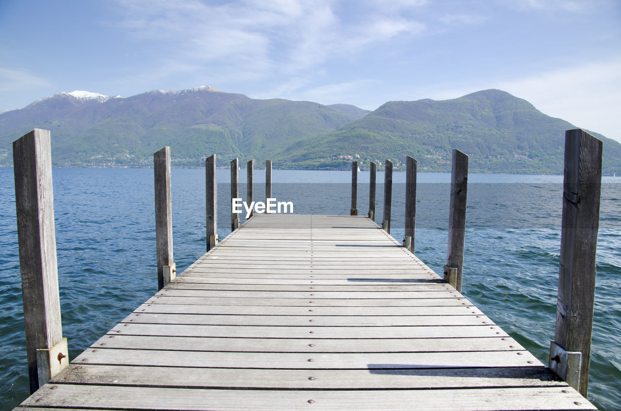 Pier On Lake Maggiore Against Mountains