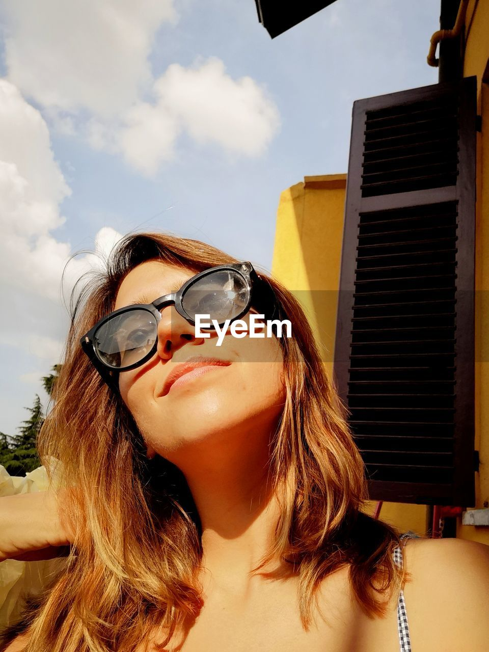Smiling Young Woman Wearing Sunglasses Against Sky During Sunny Day