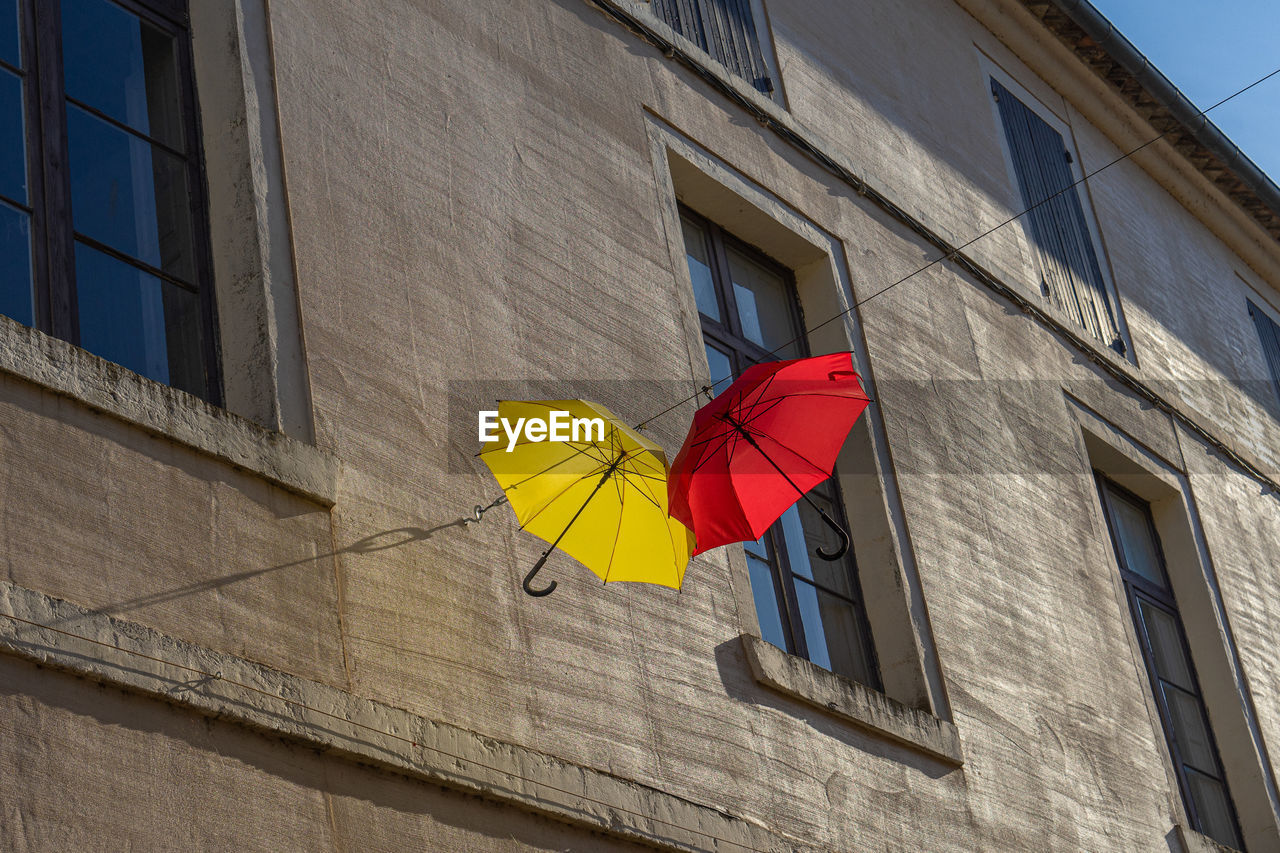 Low angle view of umbrella hanging on building