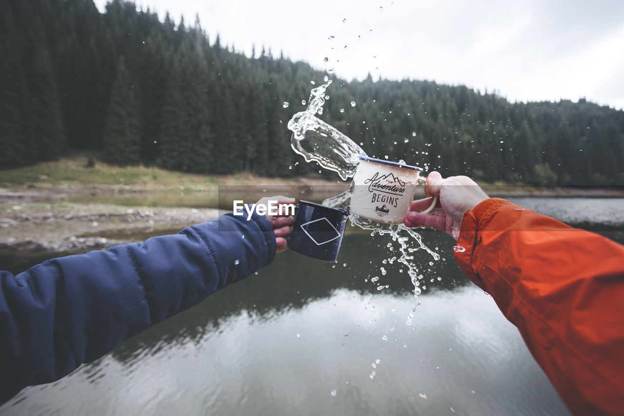Cropped Hands Splashing Water Over Lake Against Trees
