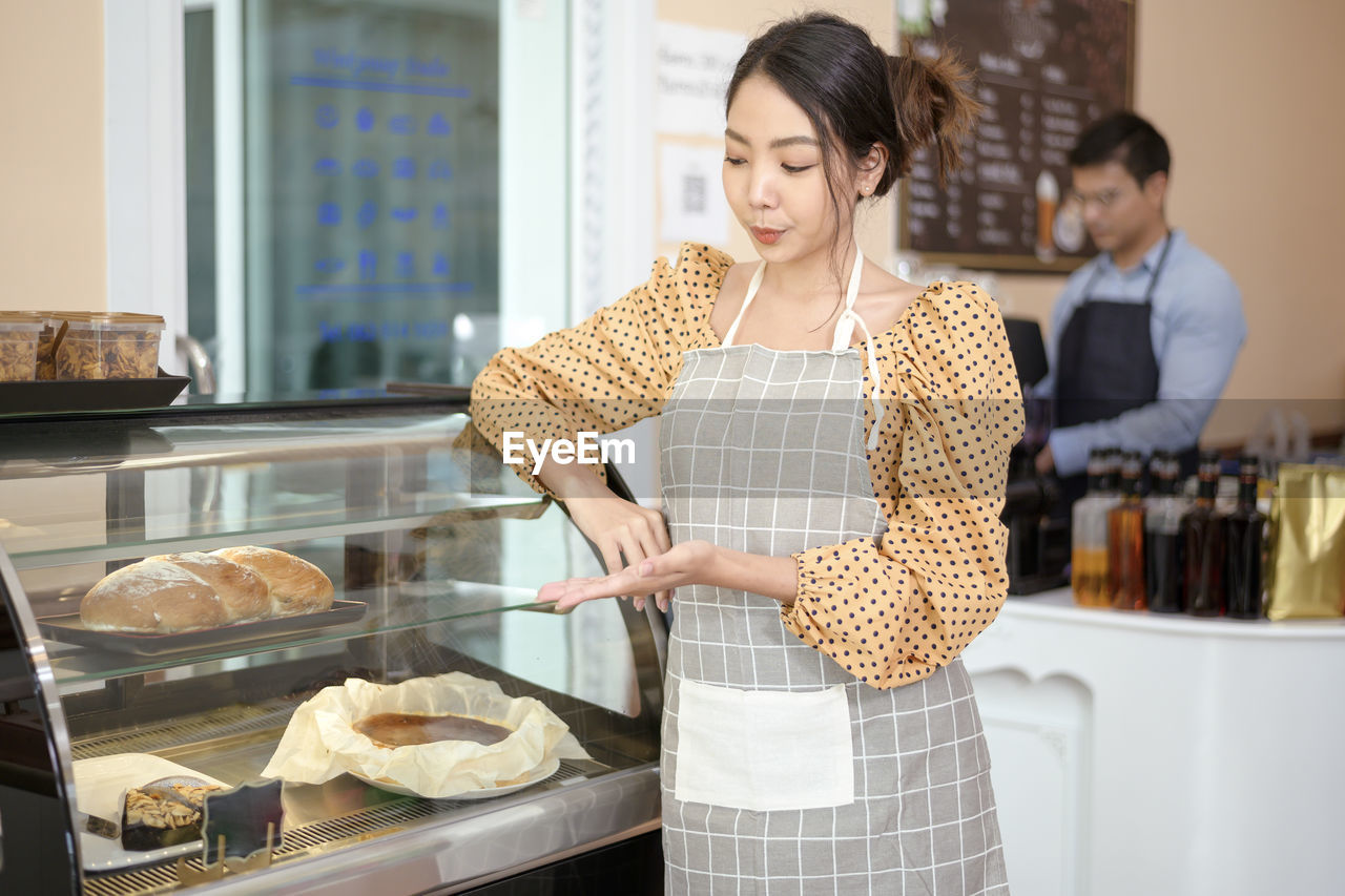 YOUNG WOMAN HOLDING FOOD AT STORE