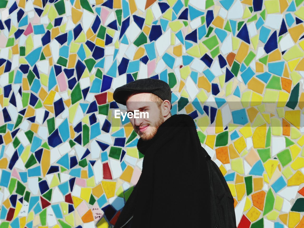 Portrait of smiling young man standing against colorful mosaic wall