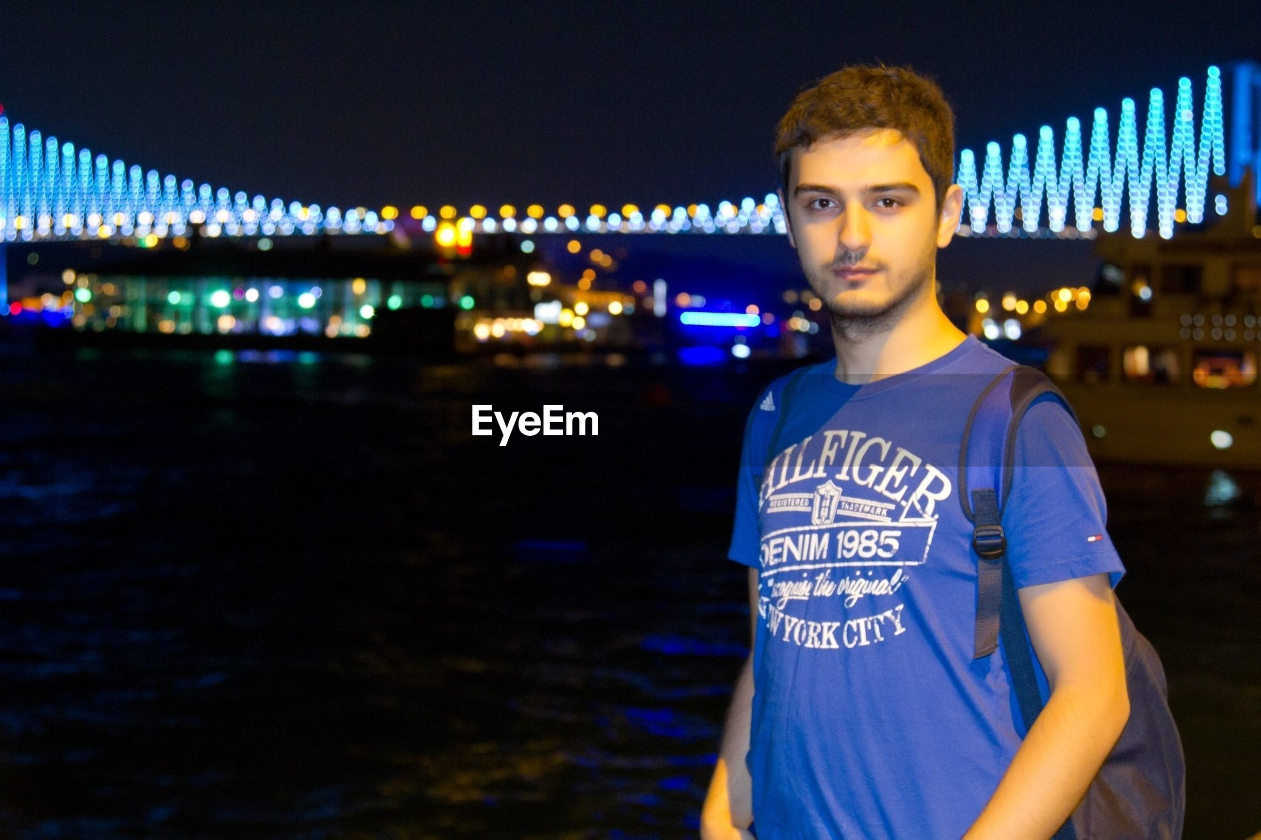 illuminated, night, lifestyles, looking at camera, portrait, casual clothing, leisure activity, person, architecture, front view, built structure, standing, building exterior, waist up, three quarter length, city, smiling, blue