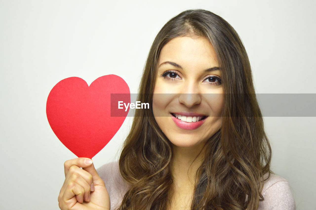 Portrait Of Beautiful Young Woman Holding Heart Shape Paper Against Gray Background