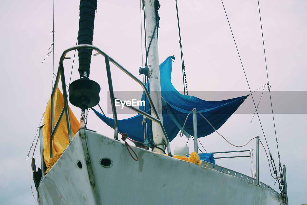 nautical vessel, transportation, mode of transportation, sky, day, moored, nature, rope, no people, water, clear sky, low angle view, mast, sailboat, outdoors, yellow, sea, ship, focus on foreground, metal, fishing boat