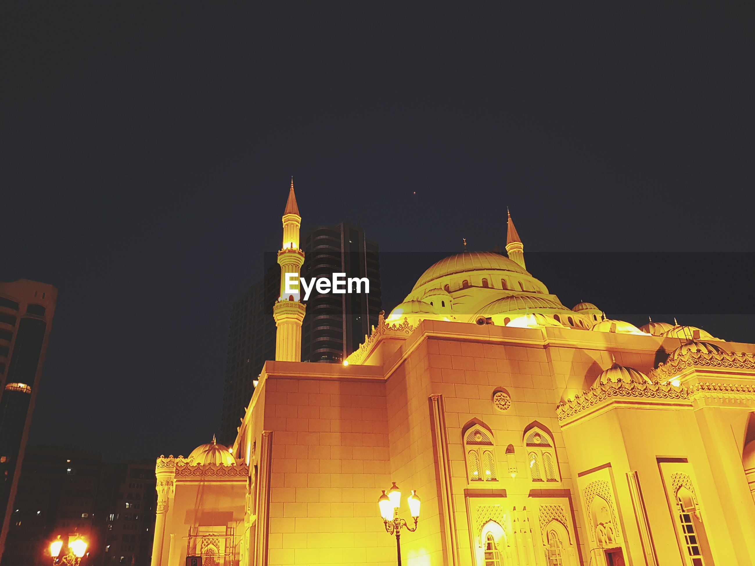 Low angle view of illuminated mosque against sky