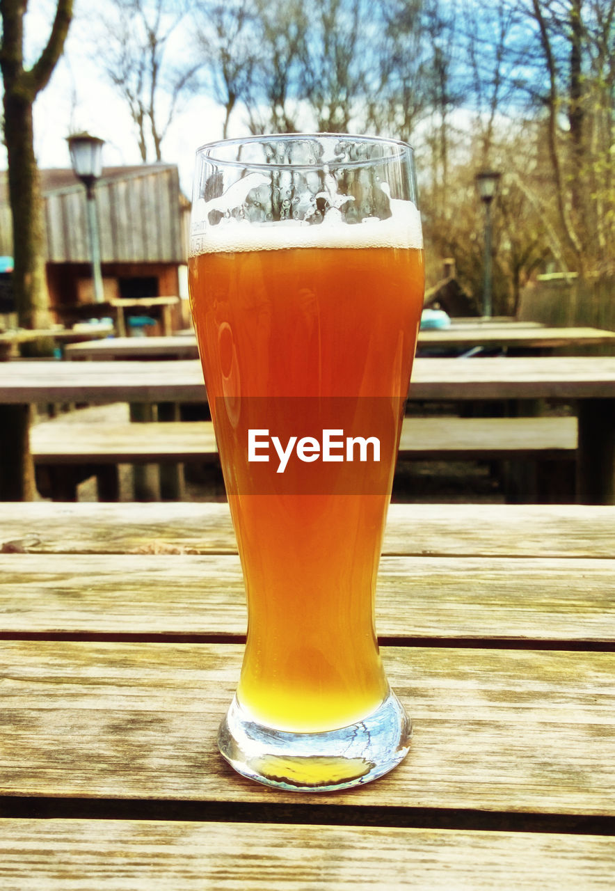 drink, refreshment, food and drink, glass, table, drinking glass, household equipment, beer, freshness, wood - material, beer - alcohol, alcohol, focus on foreground, no people, still life, close-up, beer glass, day, orange color, outdoors