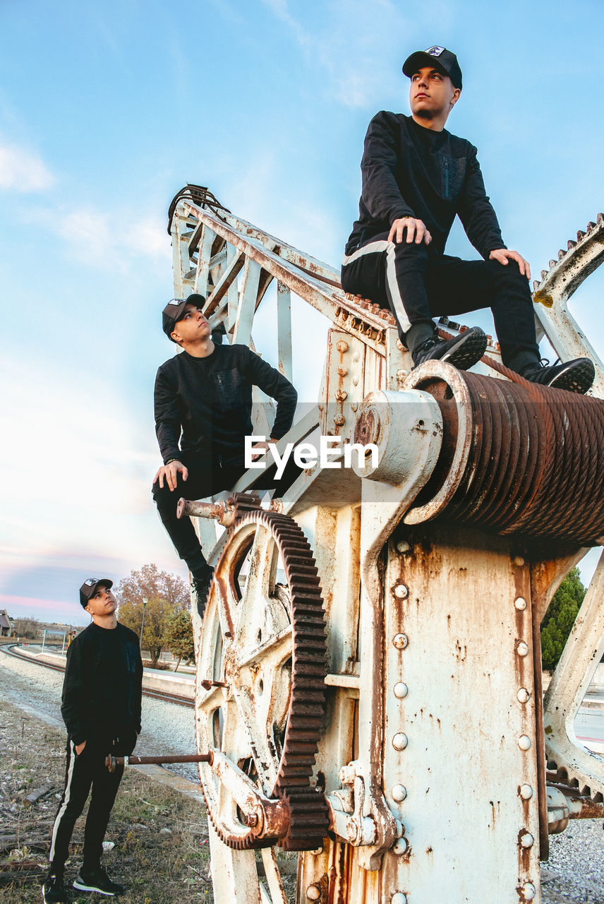 real people, sky, standing, young men, casual clothing, young adult, lifestyles, men, day, people, nature, leisure activity, three quarter length, males, full length, adult, cloud - sky, fashion, front view, outdoors