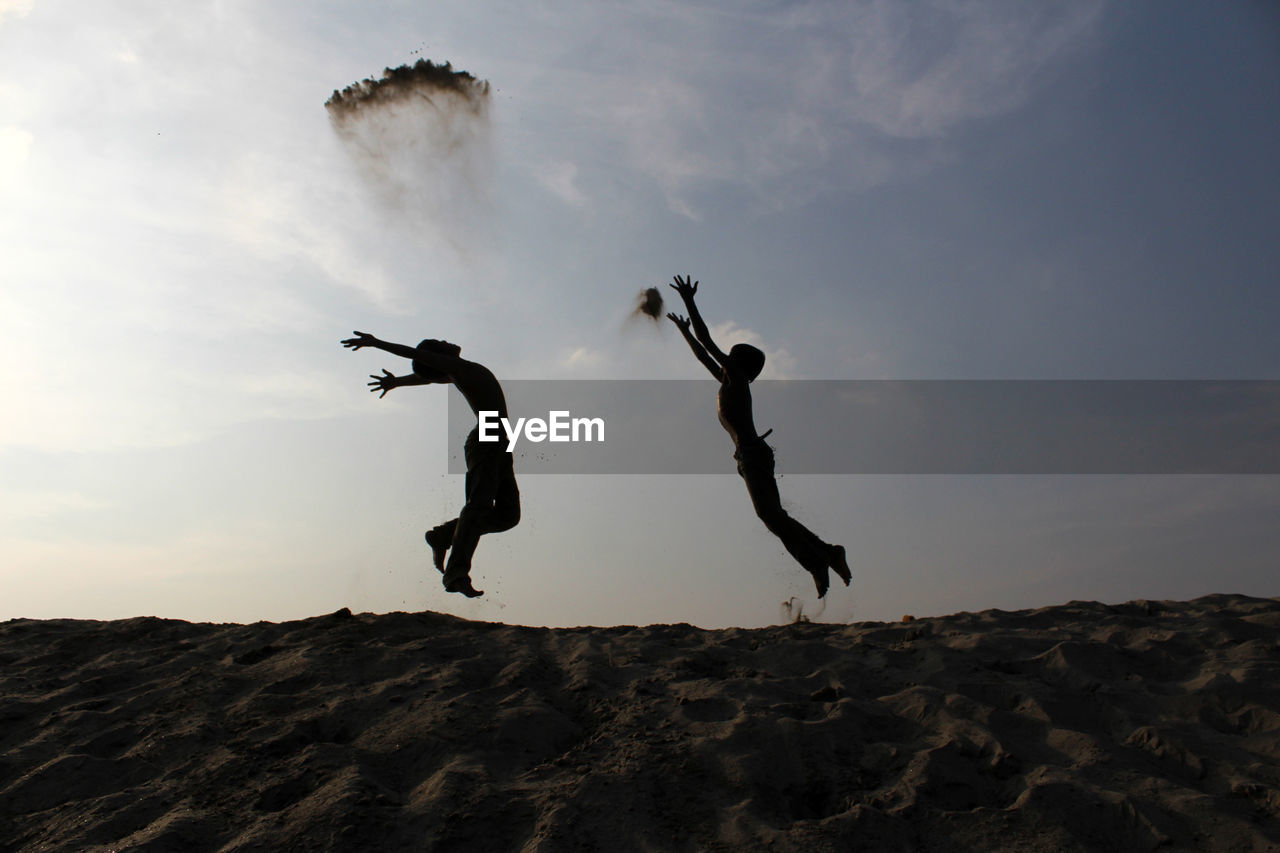 Silhouette boys jumping at beach against sky during sunset