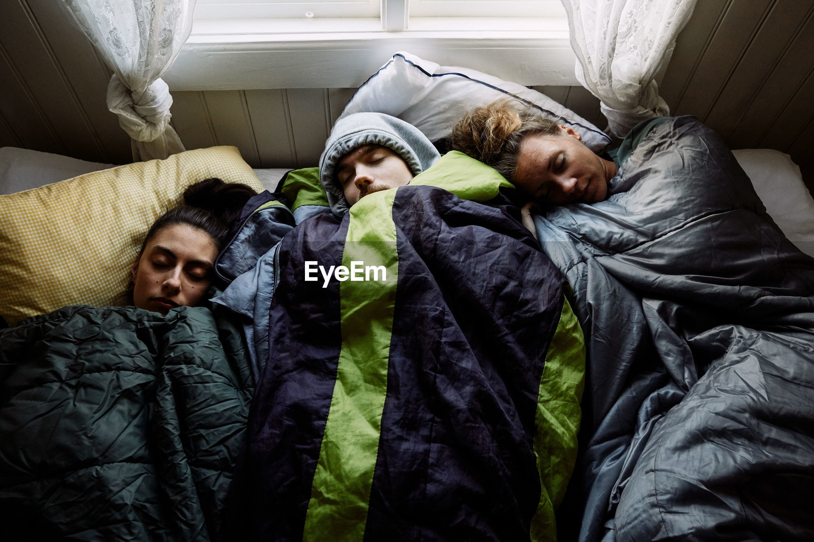 HIGH ANGLE VIEW OF PEOPLE RESTING ON BED