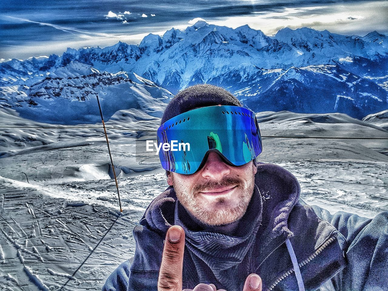 Portrait Of Man In Ski Goggles Gesturing Against Snow Covered Mountains