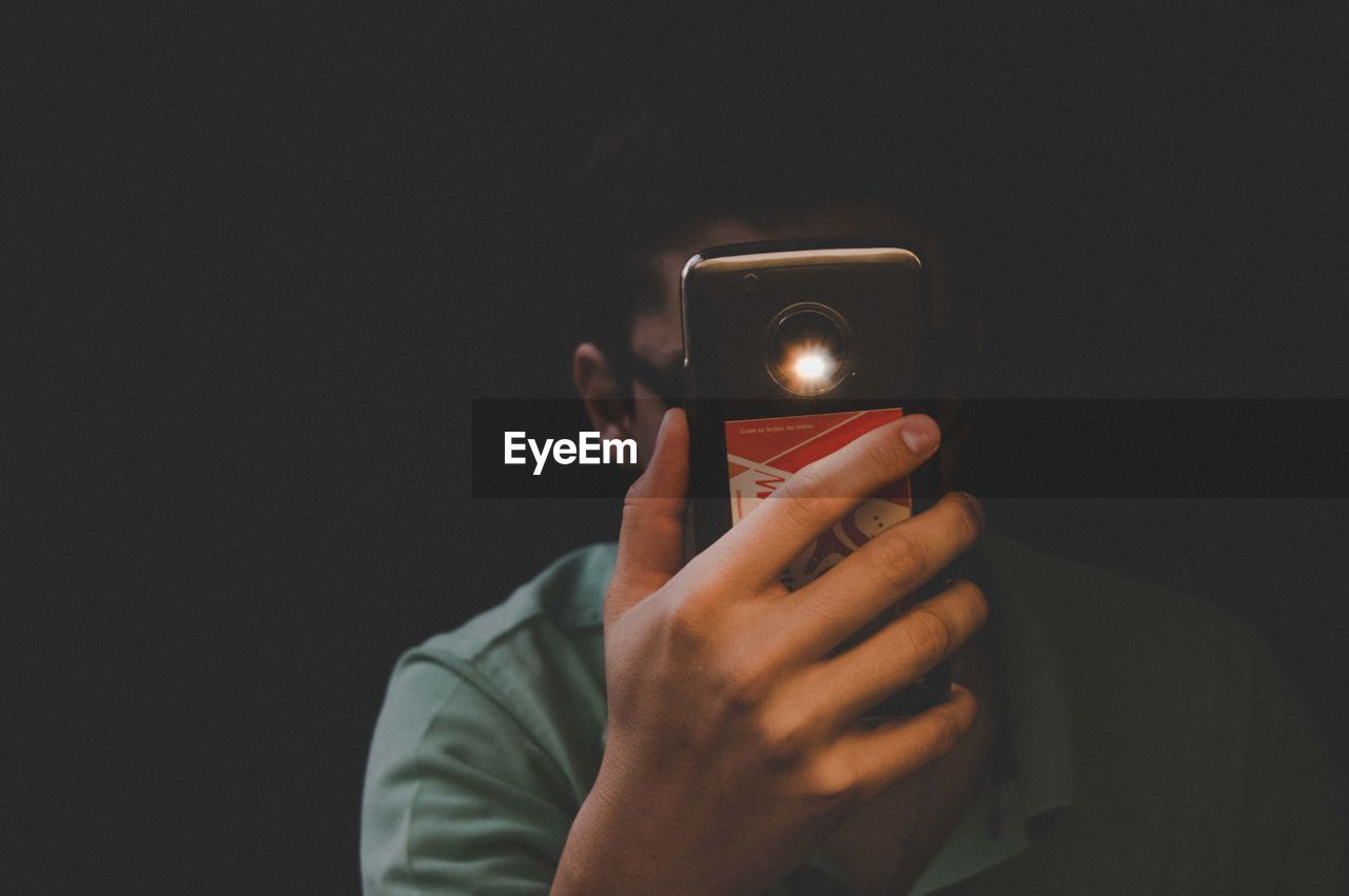 MAN HOLDING MOBILE PHONE AGAINST BLACK BACKGROUND
