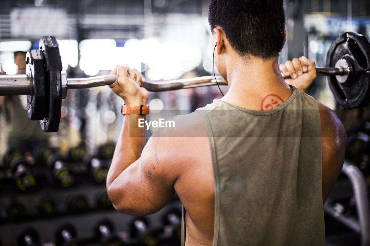 Rear View Of Muscular Build Man Lifting Barbell At Gym
