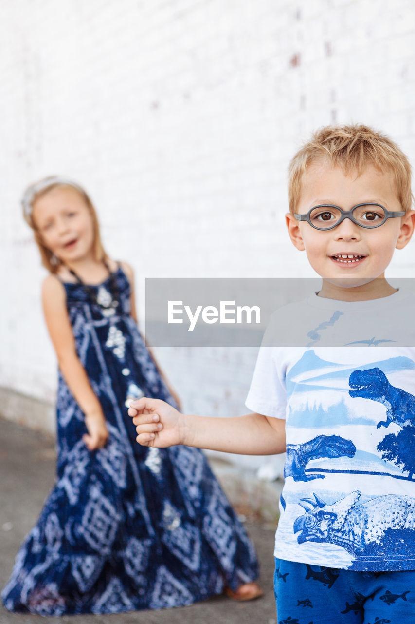 Portrait of smiling boy standing against sister on sidewalk