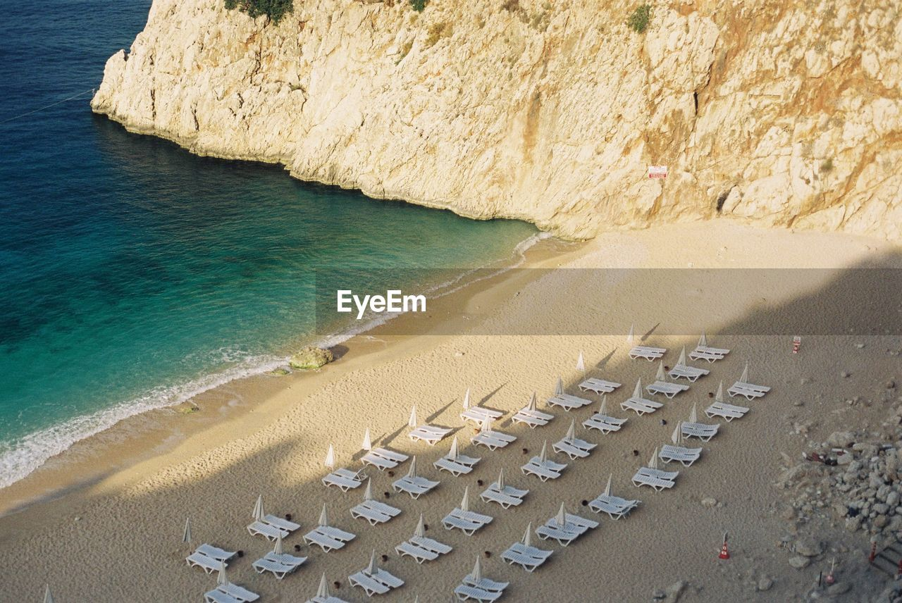 High Angle View Of Deck Chairs With Parasols Arranged At Beach