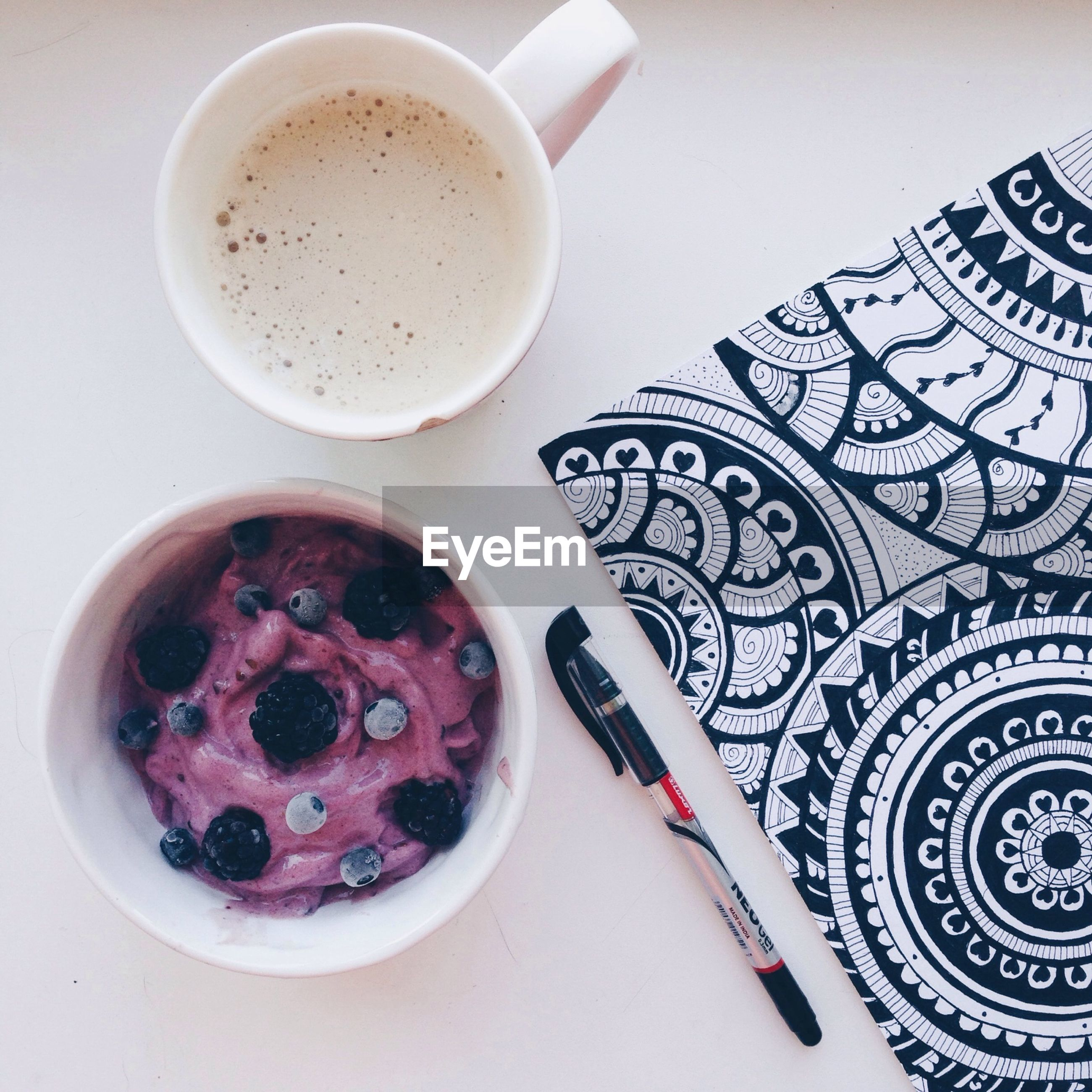 High angle view of berry yogurt with coffee cup and note pad on table