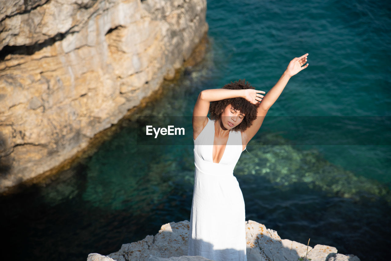 High Angle View Of Woman With Arms Raised Standing On Cliff Against Sea