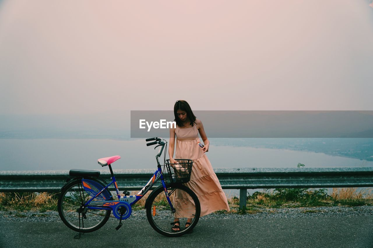 WOMAN ON BICYCLE BY SEA AGAINST SKY