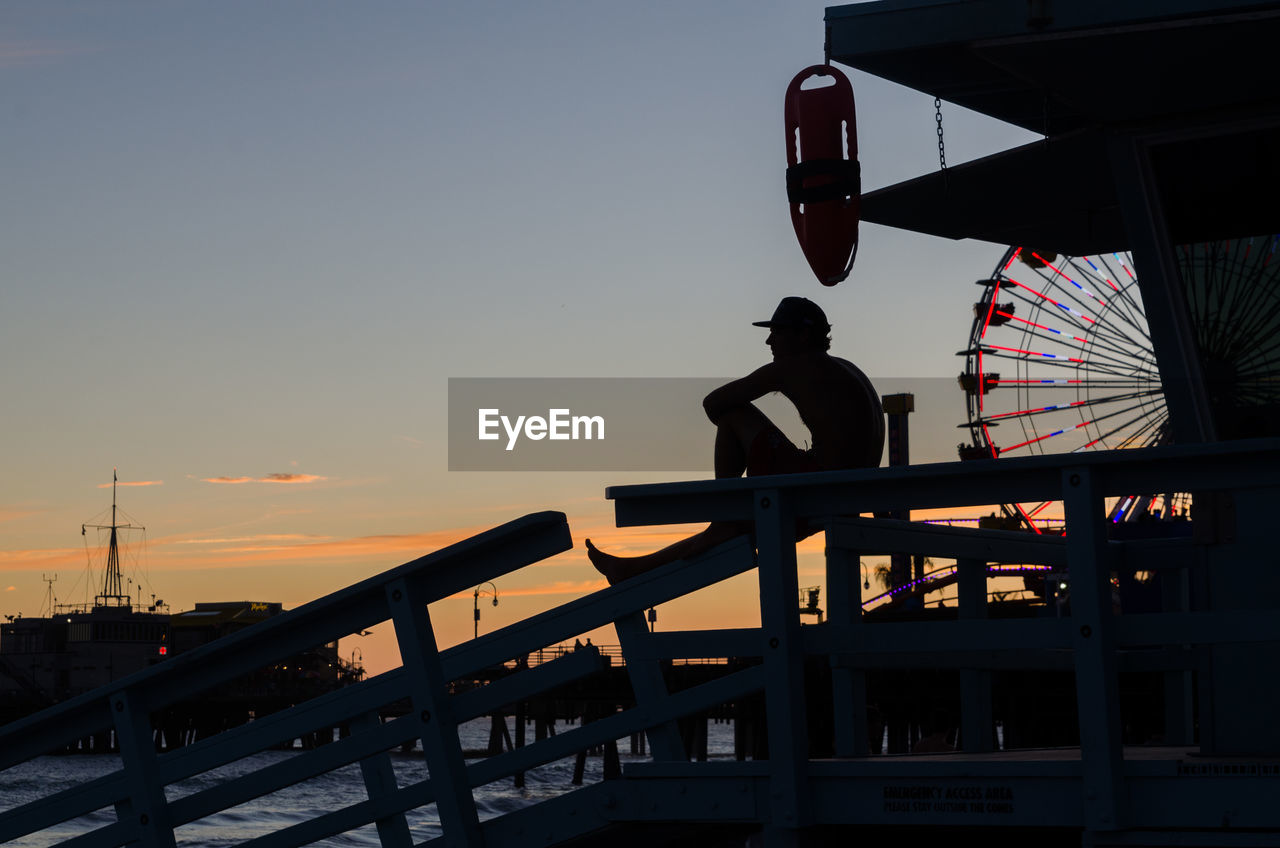 Silhouette Man Sitting At Santa Monica Pier Against Sky During Sunset
