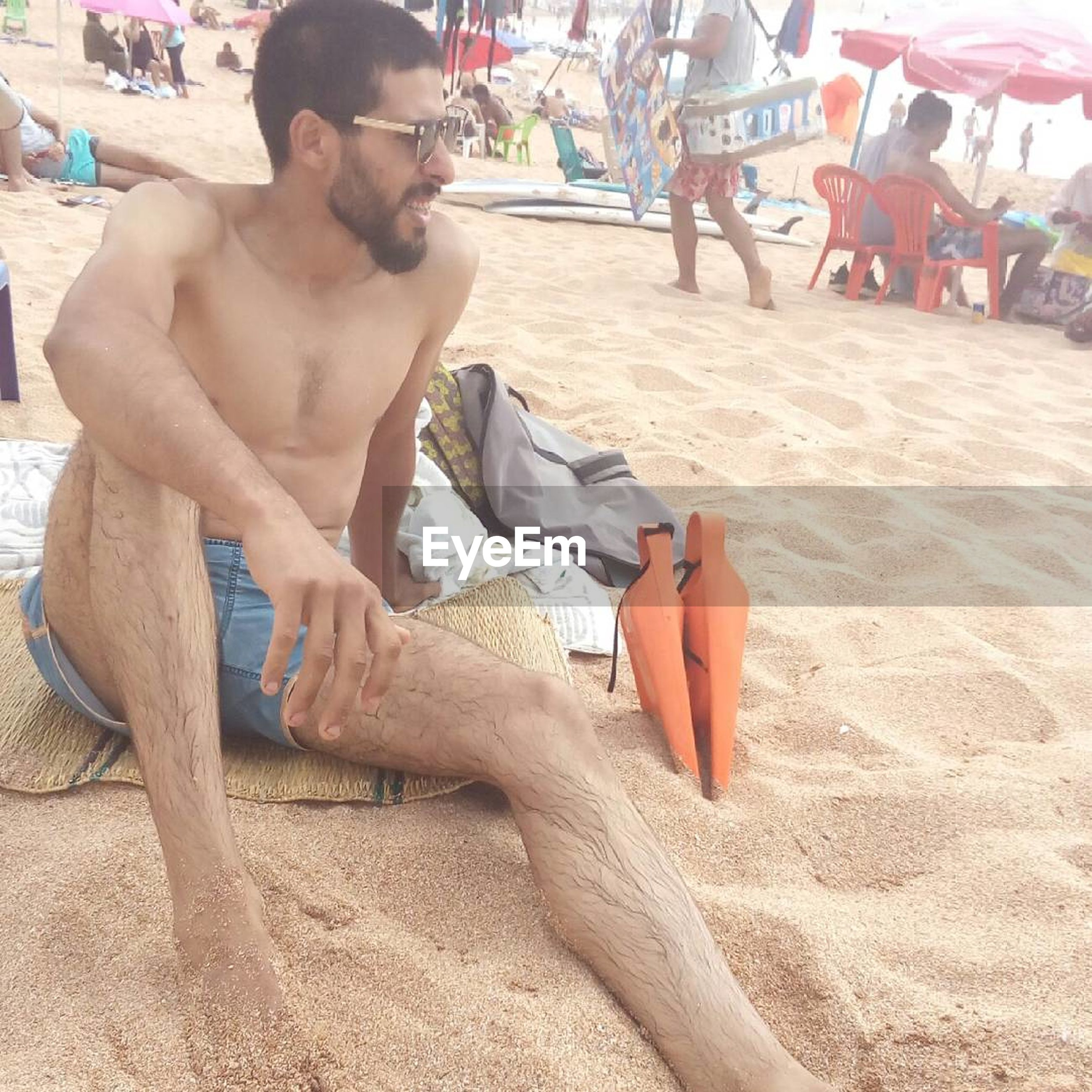 real people, sitting, sand, shirtless, outdoors, beach, leisure activity, day, one person, full length, lifestyles, vacations, young adult, people