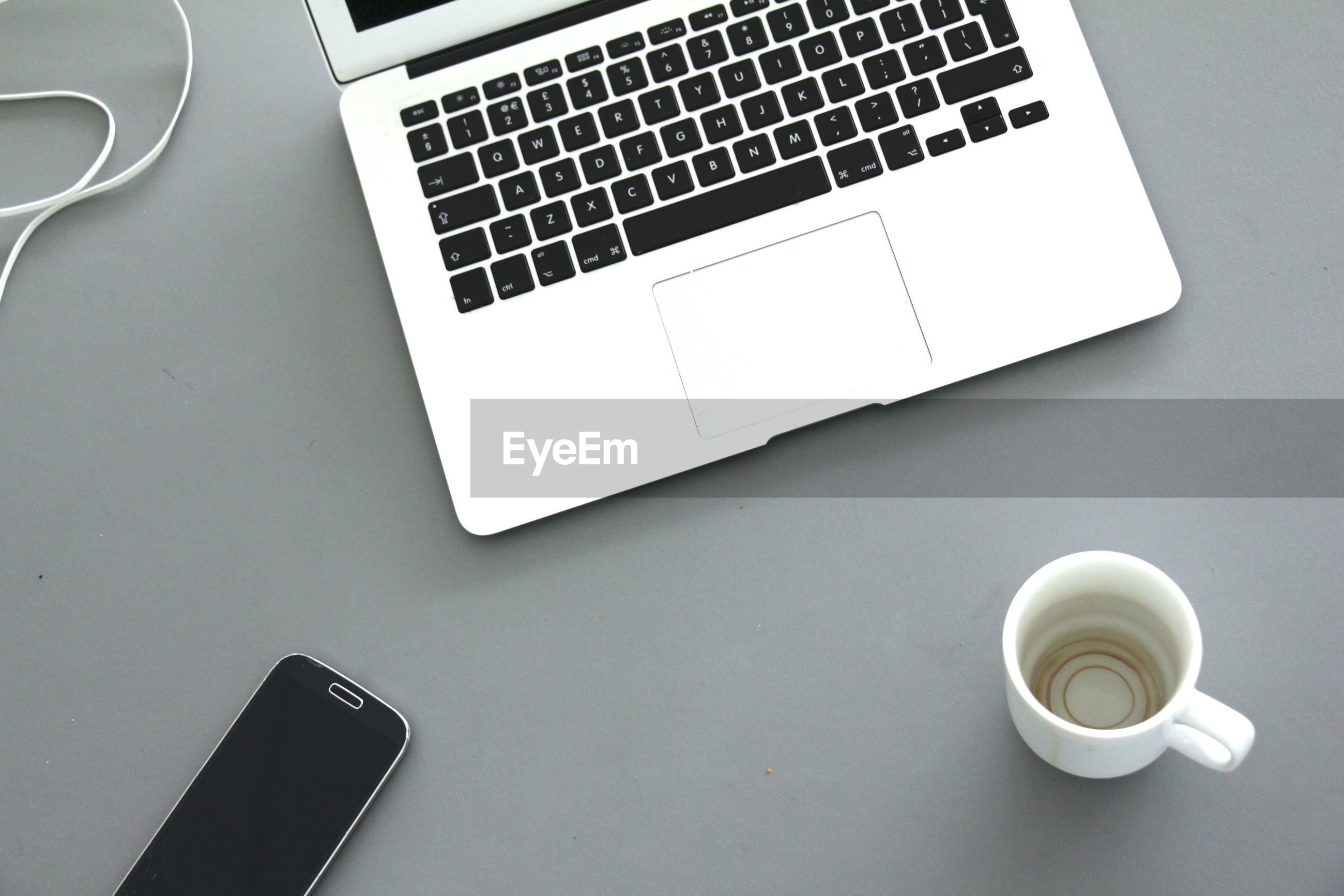 High angle view of empty cup with laptop and mobile phone on table