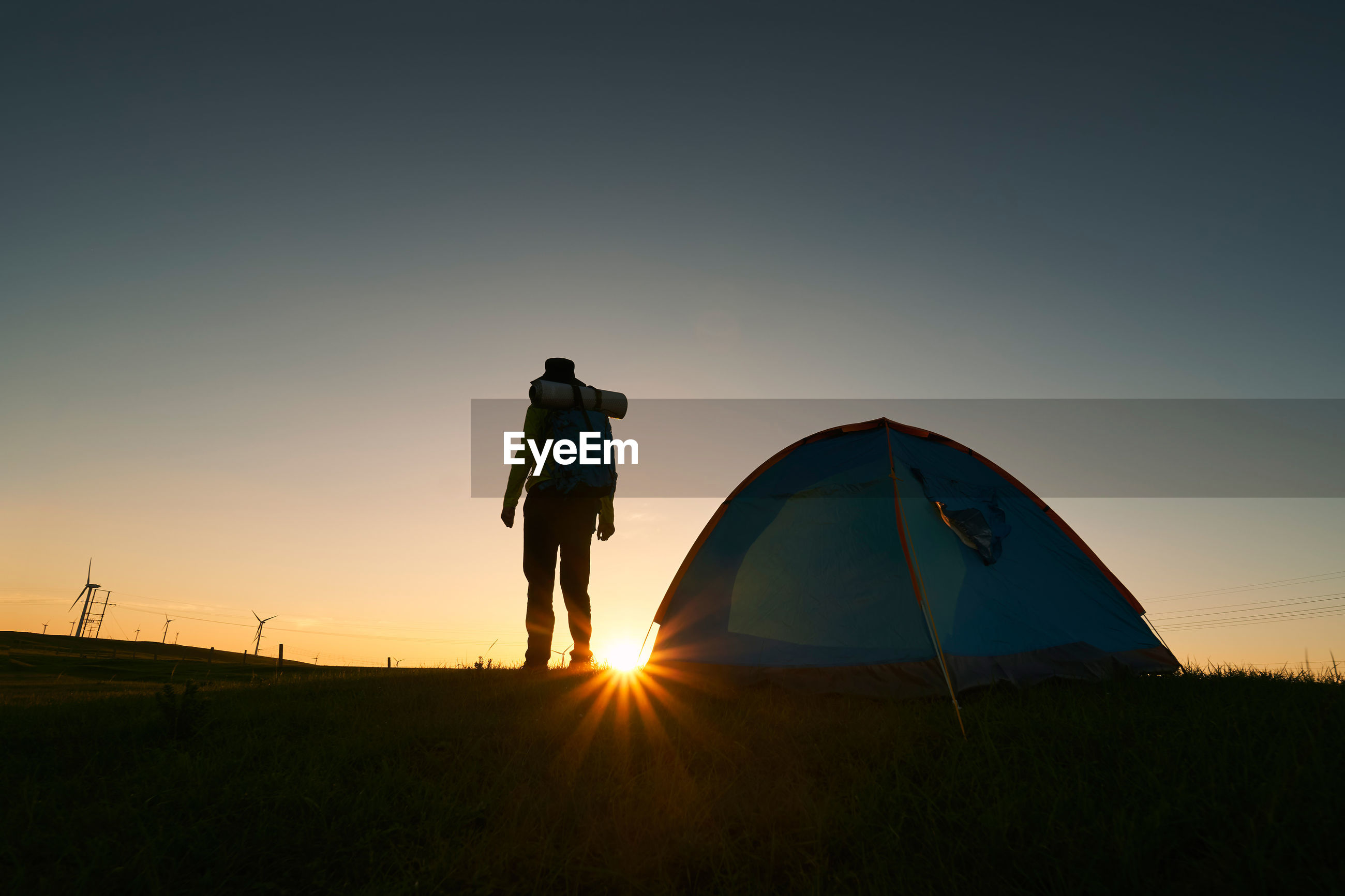 Rear view of silhouette man standing by tent on field during sunrise