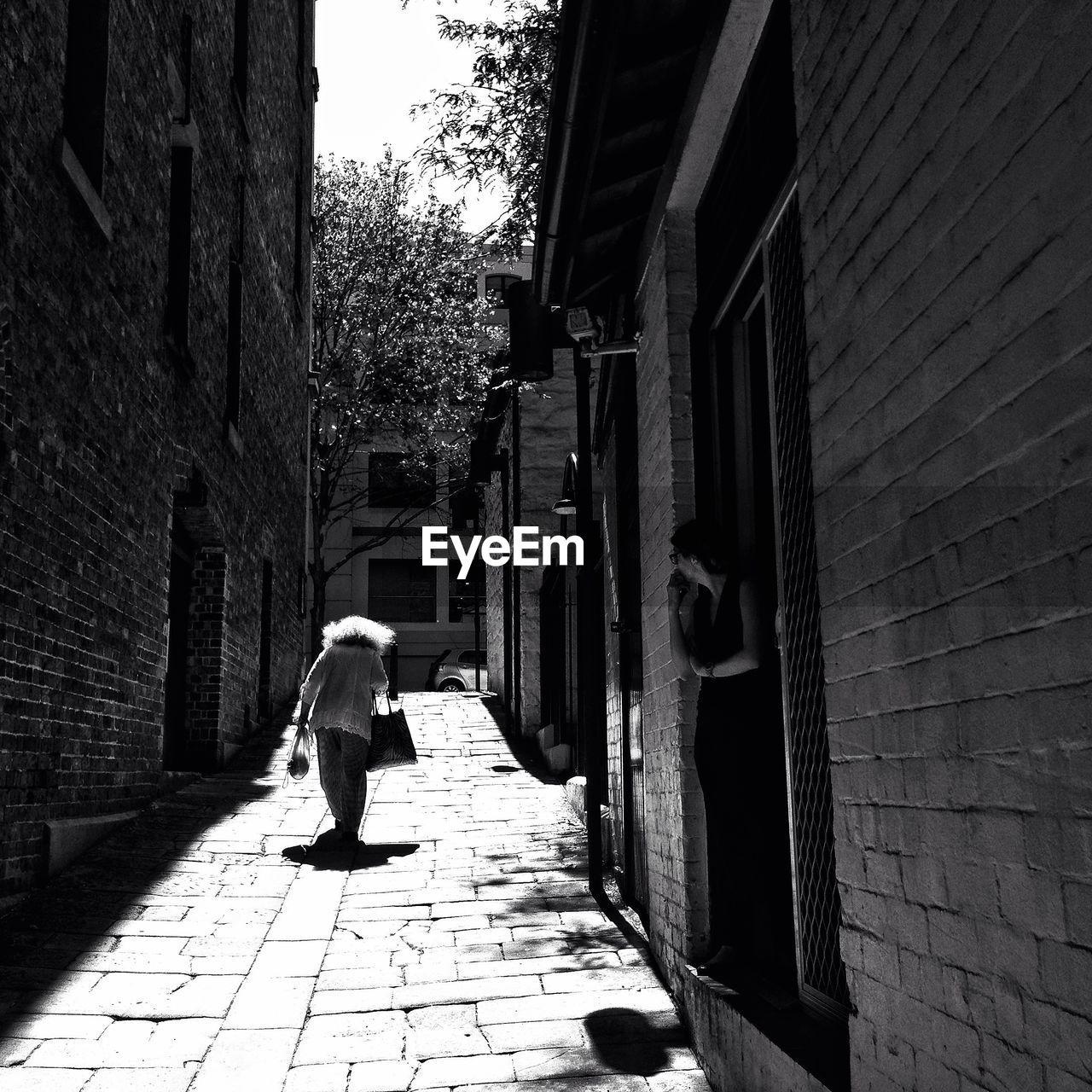 Woman walking on narrow street
