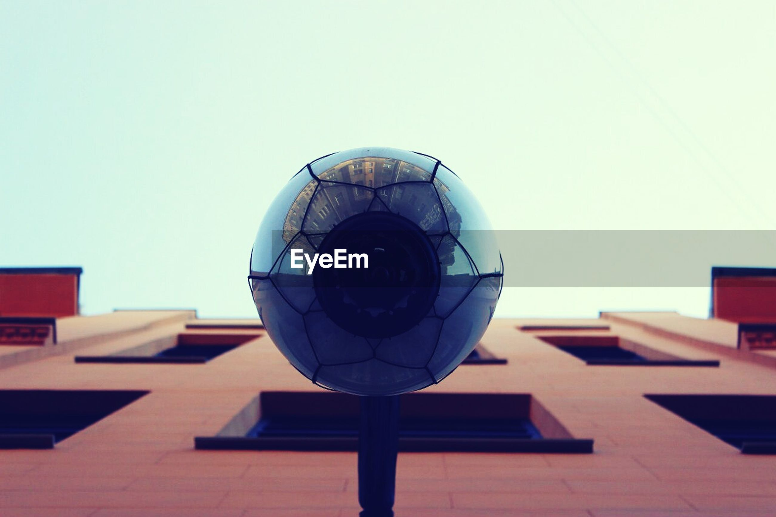 clear sky, built structure, architecture, low angle view, copy space, circle, building exterior, geometric shape, directly below, blue, mid-air, sphere, day, outdoors, lighting equipment, sky, no people, round, shape, roof
