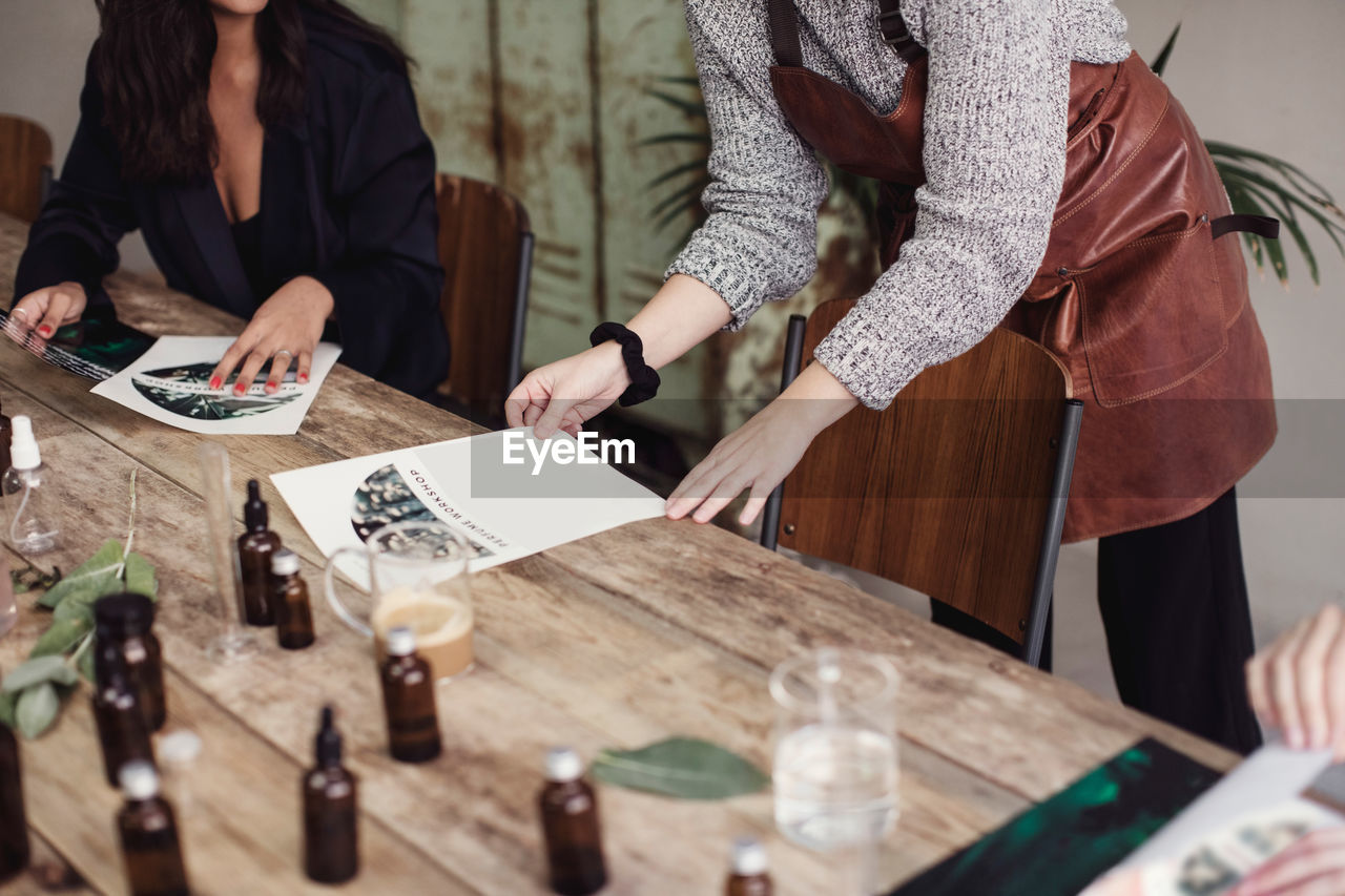 table, midsection, real people, women, business, indoors, adult, people, selective focus, holding, men, standing, togetherness, wood - material, human hand, casual clothing, finance, communication