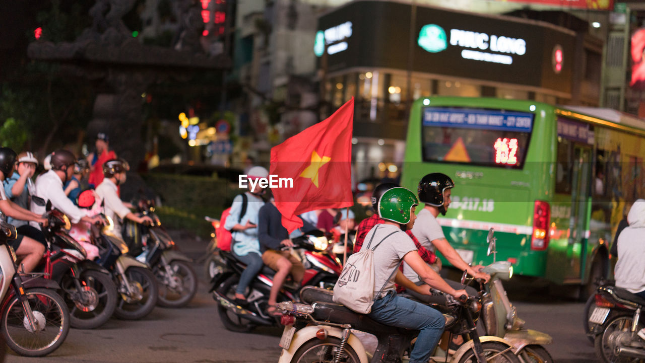 real people, men, city, mode of transport, flag, motorcycle, street, land vehicle, large group of people, transportation, built structure, building exterior, outdoors, city life, bicycle, architecture, women, lifestyles, protestor, crowd, sitting, night, biker, riot, people