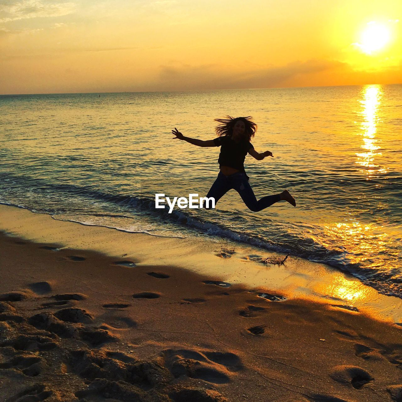 Cheerful woman jumping at beach against sky during sunset