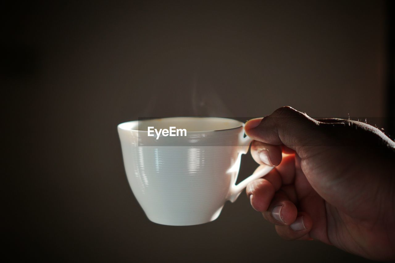 cup, hand, human hand, mug, human body part, drink, one person, coffee cup, food and drink, coffee, holding, coffee - drink, indoors, real people, refreshment, copy space, body part, lifestyles, close-up, unrecognizable person, finger, human limb, tea cup, drinking, crockery