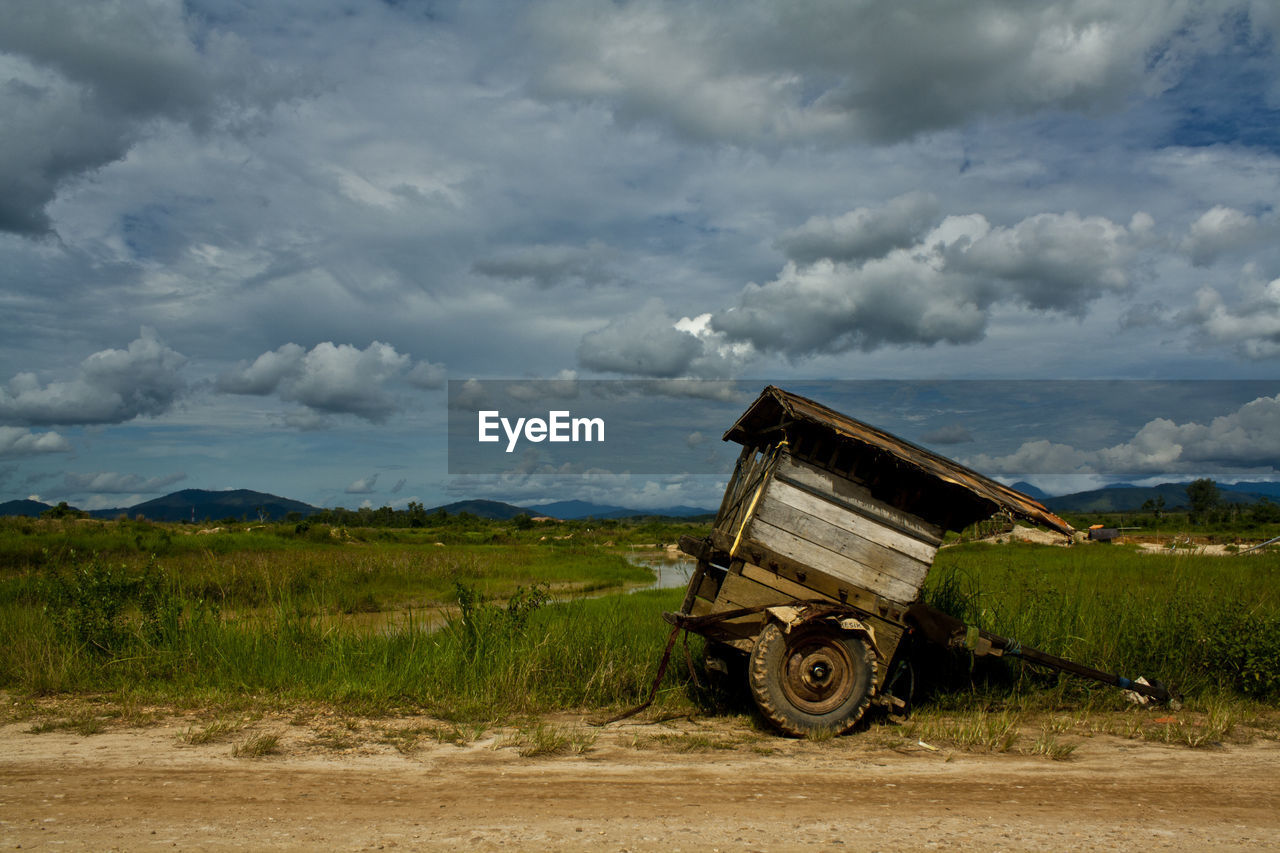 cloud - sky, sky, landscape, land, environment, field, grass, transportation, nature, day, rural scene, mode of transportation, scenics - nature, land vehicle, plant, agriculture, agricultural machinery, non-urban scene, green color, no people, outdoors, wheel