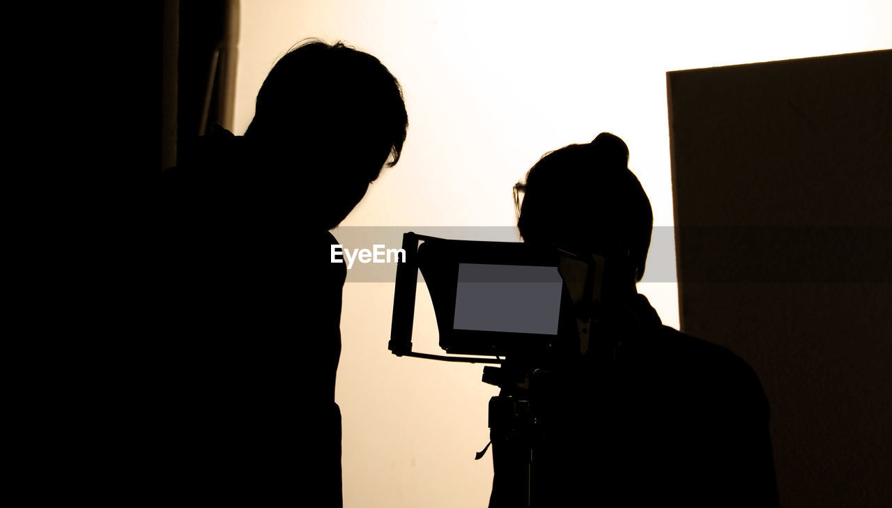 technology, silhouette, indoors, photography themes, men, real people, two people, adult, women, photographing, lifestyles, camera - photographic equipment, photographic equipment, people, standing, leisure activity, screen, activity, occupation, camera, digital camera, photographer, filming, behind the scenes