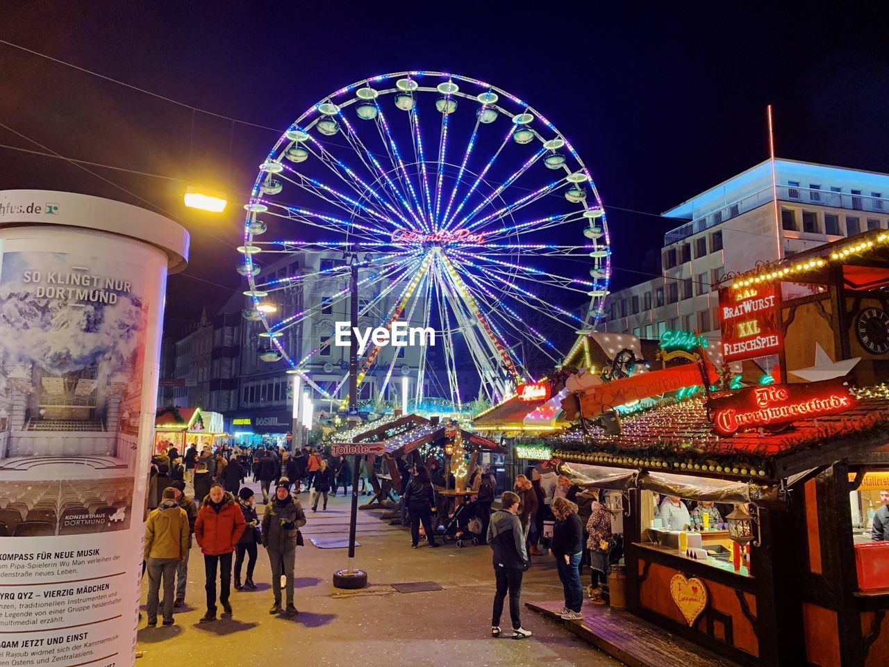 group of people, amusement park, amusement park ride, illuminated, night, arts culture and entertainment, real people, large group of people, crowd, leisure activity, sky, built structure, men, architecture, ferris wheel, city, lifestyles, women, adult, outdoors