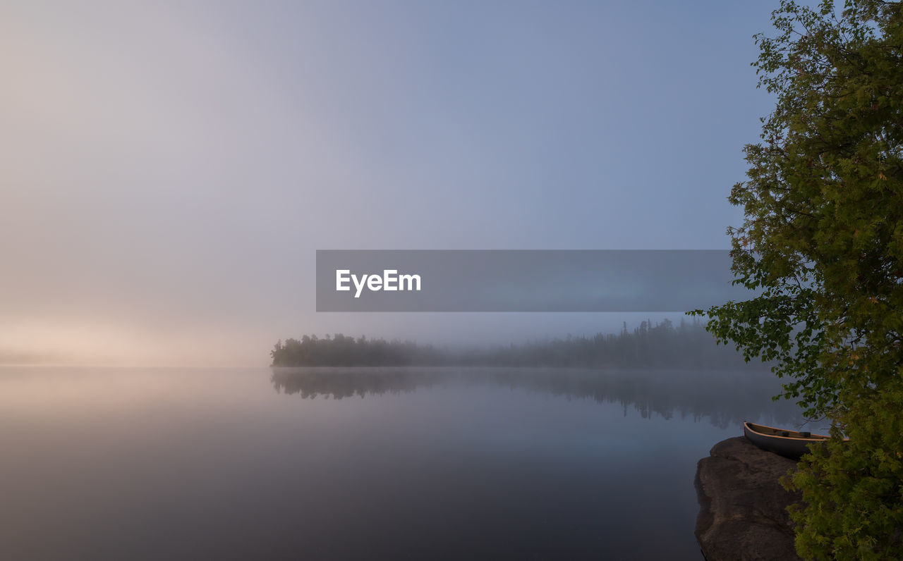 water, sky, tranquility, beauty in nature, tranquil scene, scenics - nature, tree, reflection, lake, plant, idyllic, nature, non-urban scene, fog, no people, waterfront, outdoors, copy space, hazy, reflection lake