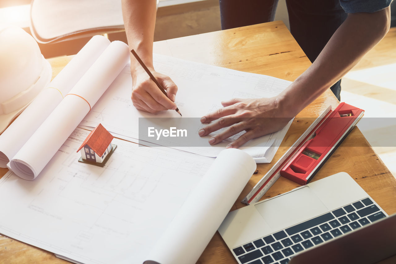 table, indoors, high angle view, real people, pen, women, working, human hand, adult, people, paper, communication, hand, occupation, midsection, laptop, human body part, wireless technology, connection, using laptop, design professional, blueprint