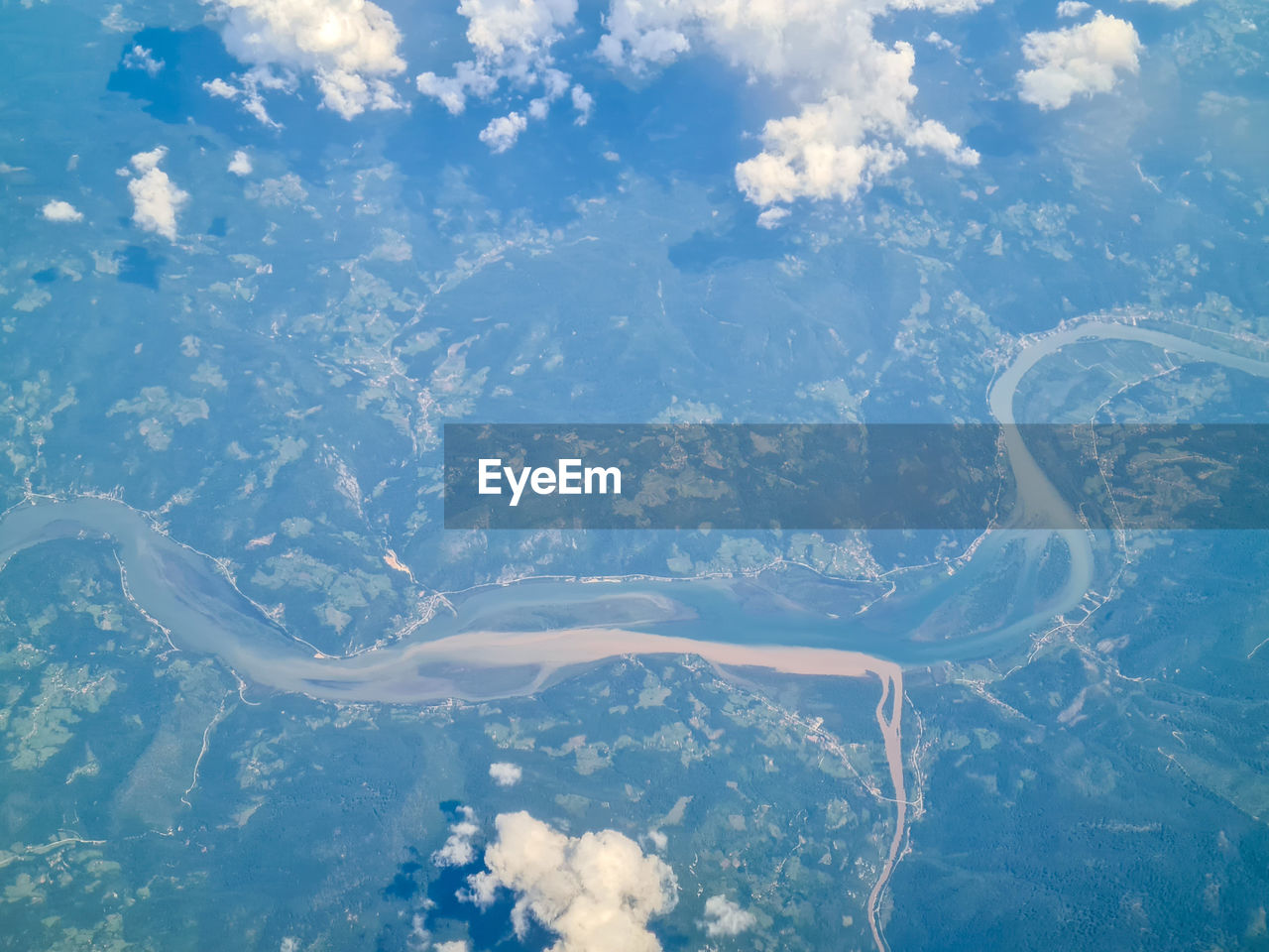 Aerial view of two rivers flowing together with clouds