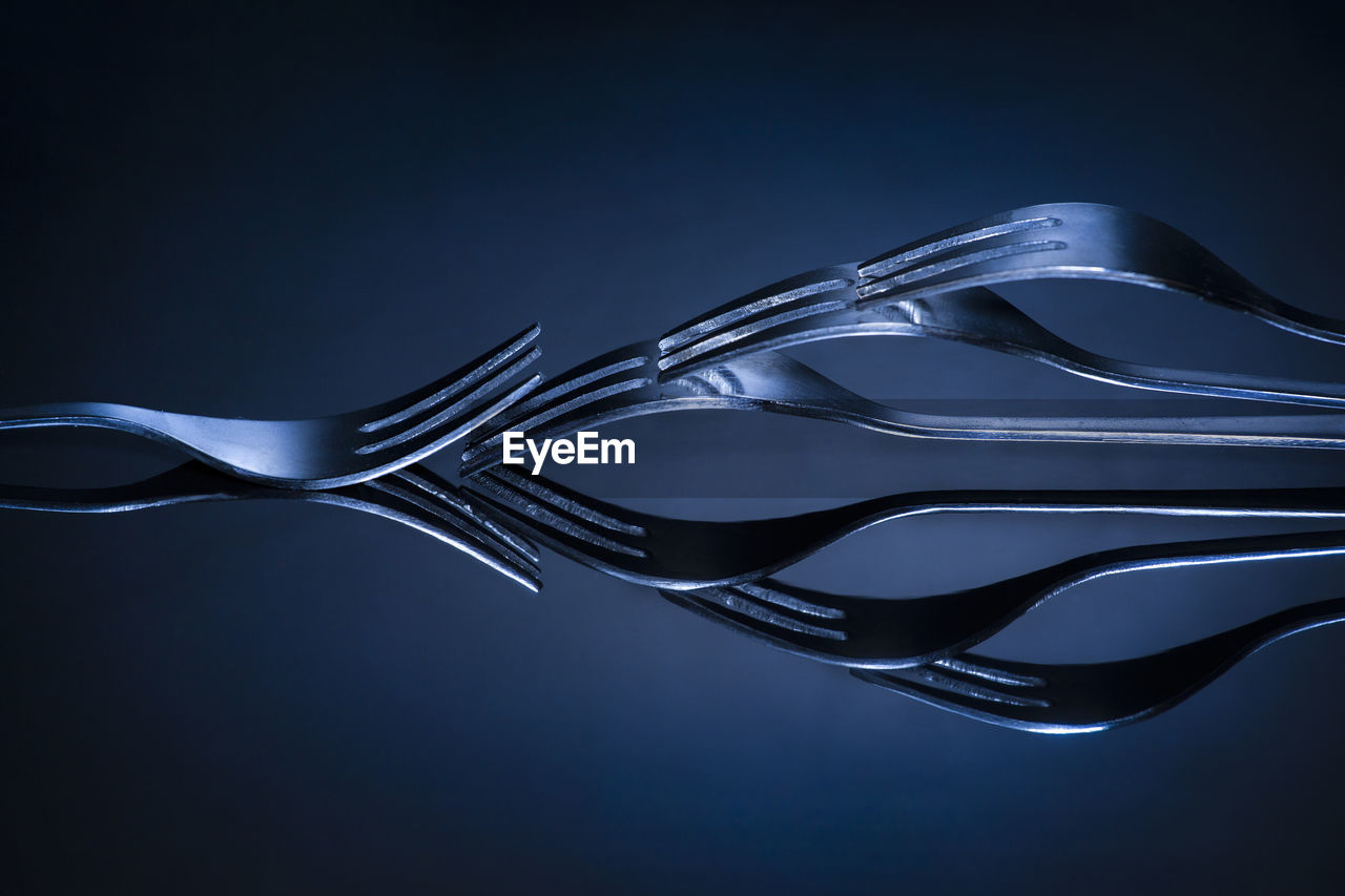 Close-Up Of Forks Arranged On Table Against Blue Background