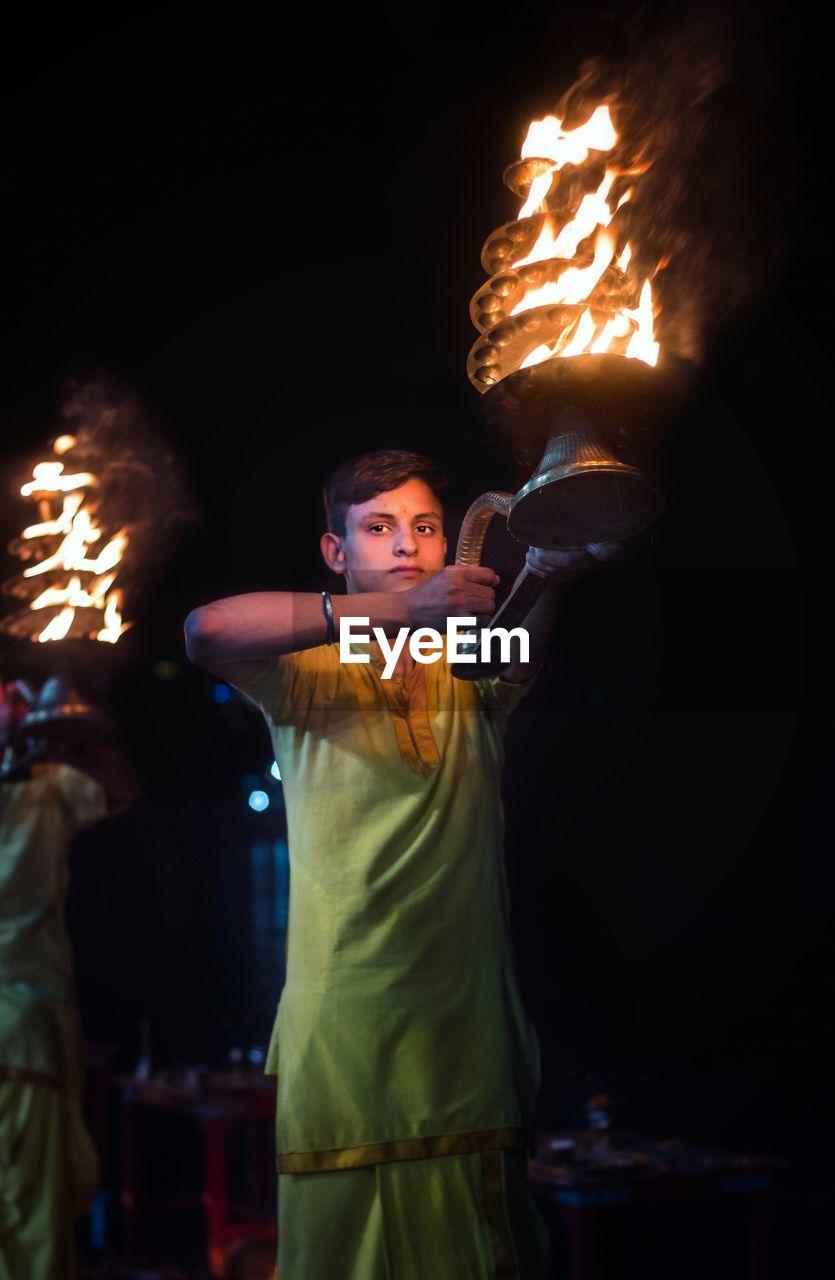 Portrait Of Man Holding Lit Diya At Night