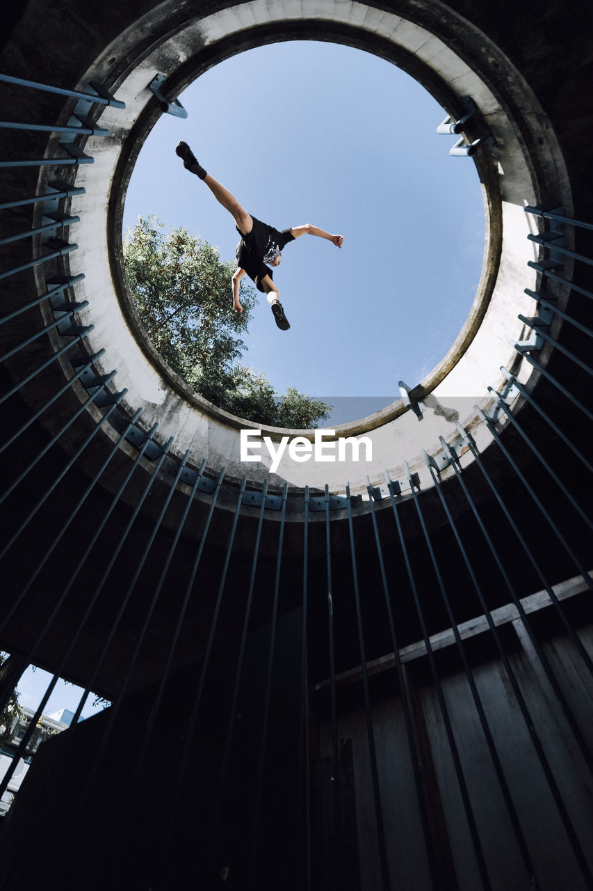 low angle view, leisure activity, full length, architecture, mid-air, lifestyles, one person, sky, built structure, day, real people, jumping, men, motion, nature, skill, stunt, sport, sunlight, outdoors, human arm