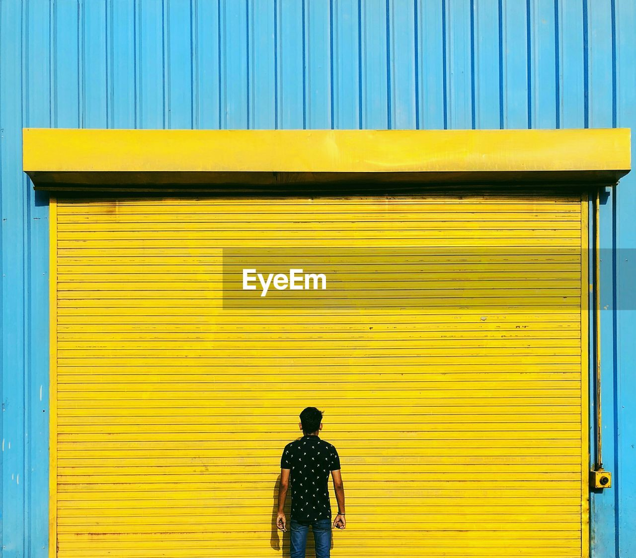 Rear View Of Man Standing Against Closed Yellow Shutter