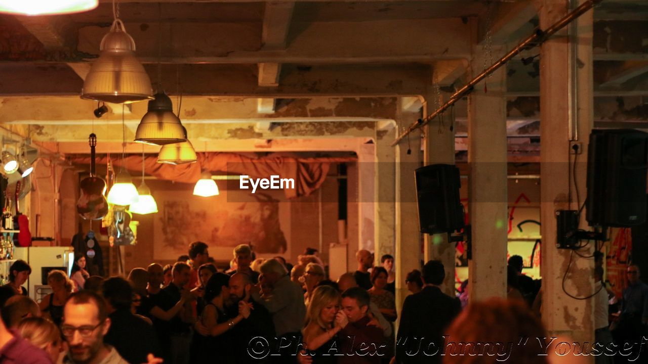 large group of people, illuminated, night, real people, indoors, men, women, built structure, hanging, architecture, crowd, people